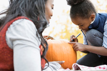 Mother And Daughter Drawing Carving Pumpkin