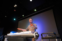Scientist Demonstrating Acoustic Waves Using A Rubens Tube In Science Center Theater