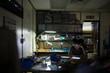 Focused female electronics engineer working at digital tablet in dark workshop