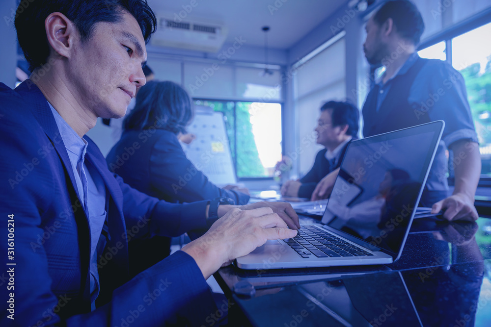 Fototapeta Businessman using computer laptop while meeting and analyzing data together in teamwork for planning and startup new project.