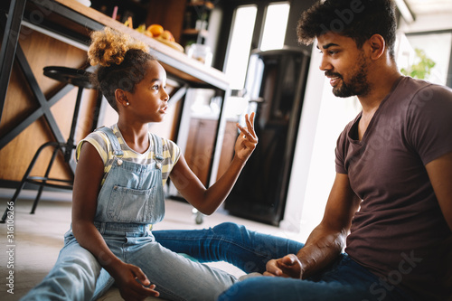 Cute african girl and her handsome father are talking and smiling at home