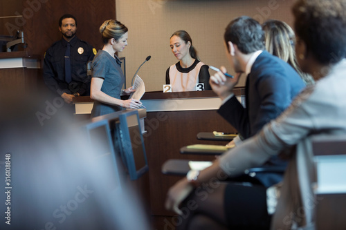 Photo Female attorney with evidence interrogating witness on the stand in legal trial