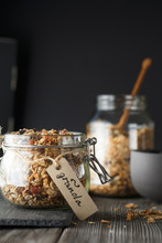Organic Homemade Granola Cereal With Oats, Nuts And Dried Berries. Muesli In A Glass Jar On The Dark Backround. Healthy Vegan Breakfast Or Snack. Proper Nutrition Concept
