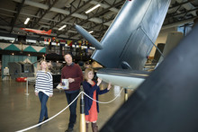 Curious Family Looking At Wing Of Airplane In Warm Museum Hangar