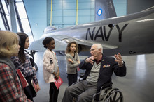 War Veteran In Wheelchair Talking To Students On Field Trip At Naval Airplane In War Museum Hangar