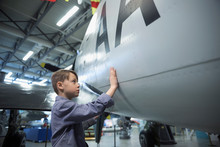 Curious Boy Touching Air Force Airplane In War Museum Hangar