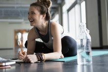 Smiling Woman Sitting On Yoga Mat Writing In Journal In Gym Studio