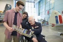 Grandfather War Veteran In Wheelchair And Grandchildren Looking At Brochure In War Veteran Museum Hangar