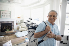Smiling Senior Man Carrying Golf Clubs In Beach House