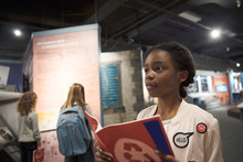 Curious African American Girl Student With Notebook On Field Trip In War Museum