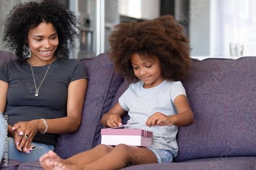 Valokuva Cute little black girl unwrap birthday present at home