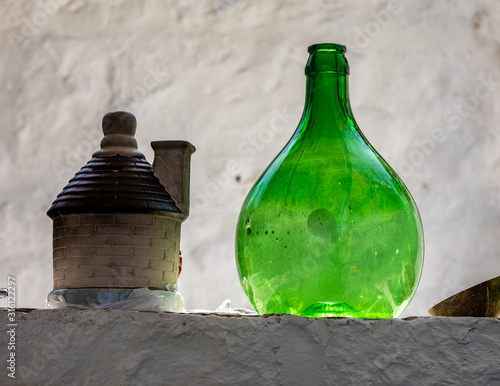 Papel de parede Demijohn wine bottle at cafe in Trulli village in Alberobello, Italy