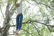 Portrait Barefoot Hipster Man Hanging From Tree