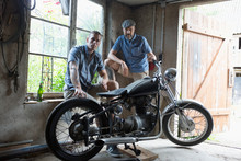 Portrait Confident Male Friends Fixing Motorcycle In Garage