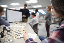 Girl Middle School Student Taking Notes In Chess Club Lesson In Library