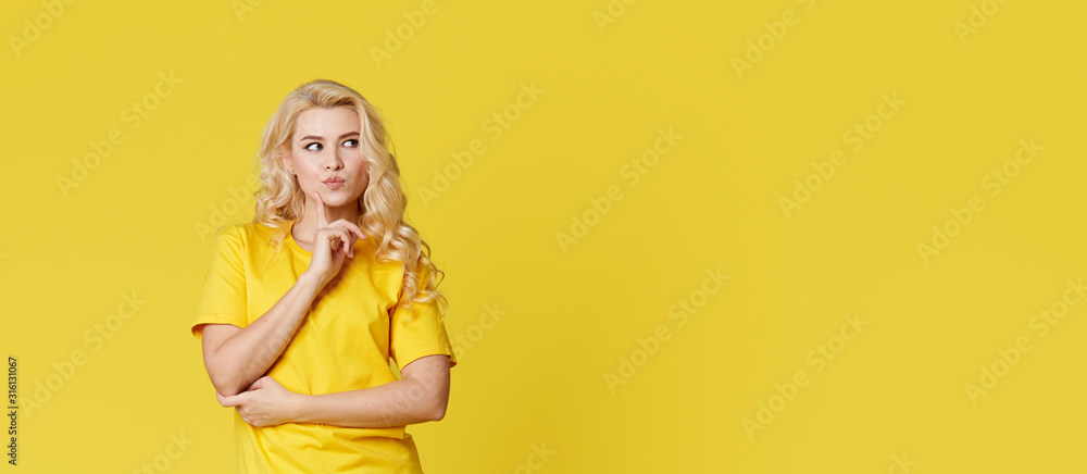 Fototapeta Photo of a happy young blond woman standing isolated over yellow wall background. Looking at the camera showing the direction of copy space. Banner