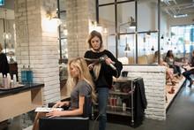Female Hair Stylist Blow Drying Hair Of Customer In Hair Salon