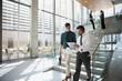 Businessmen walking, using digital tablet in modern office lobby