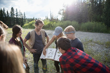 Teachers Showing Plant Photographs To Teenage Outdoor School Students In Sunny Field