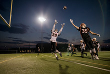 Teenage Boy High School Football Player Receiver Jumping To Catch The Ball On Football Field