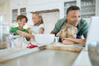 Happy children preparing cookie dough while father and brother use laptop at kitchen counter