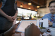 Female customer paying, signing digital tablet credit card swiper at restaurant table