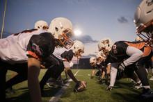 Teenage Boy High School Football Players Ready To Snap The Ball On Football Field