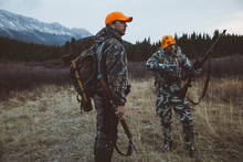 Male Hunter Friends In Camouflage Carrying Hunting Rifles In Remote Field Below Mountains