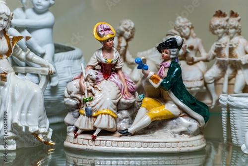 Fotomural Assortment of rare porcelain figurines on glass shelf