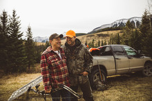 Smiling Father And Son Hunters With Bow And Arrow Near Truck In Remote Field Below Mountain