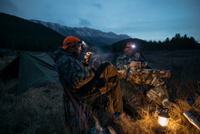 Male Hunter Friends In Headlamps Smoking Pipes At Campsite In Remote Field Below Mountains At Night