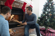 Father And Son Building A Fire In Fireplace In Christmas Living Room