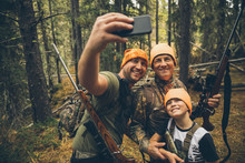 Multi-generation Male Hunters With Hunting Rifles Taking Selfie With Camera Phone In Forest