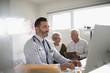 Male doctor working at laptop with senior couple patient in background in doctor