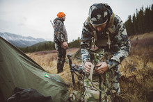 Male Hunters Preparing Backpack And Equipment Outside Tent At Campsite In Field