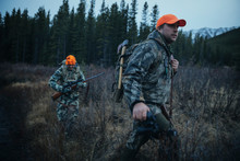 Male Hunter Friends In Camouflage With Hunting Rifle And Ax Walking In Remote Field