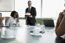 Businessman Serving Birthday Cake To Surprised Businesswoman In Conference Room