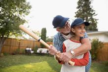 Grandfather Teaching Grandson Baseball, Holding Bat In Backyard