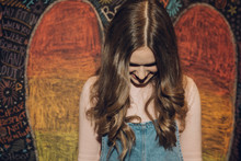 Smiling, Shy Caucasian Brunette Tween Girl Against Wall With Chalk Wings