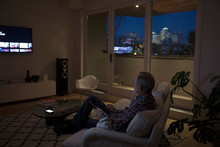 Senior Man Watching TV In Dark Urban Apartment
