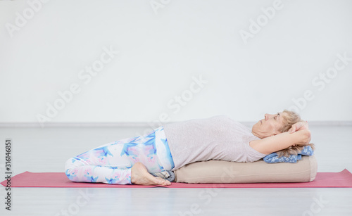 Senior woman practicing yoga, lying in Reclined Butterfly exercise Fotobehang