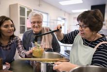 Female Volunteers Cooking, Pou...