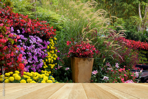 Empty top wooden table on tropical colorful flowers blooming in garden