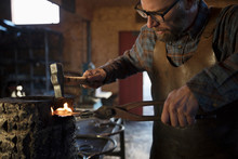 Male Blacksmith Shaping Metal With Tongs And Hammer In Blacksmith Shop