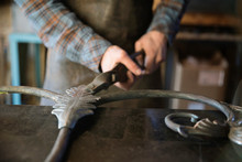 Male Blacksmith Hand Shaping Scrolled Metal