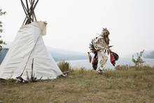 Native American Indian In Traditional Clothing Outside Teepee With River View