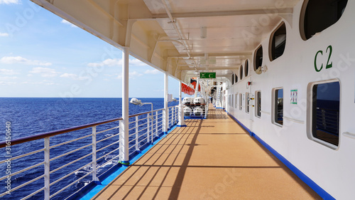 Fototapeta promenade deck on a cruise ship. safety on the ship, lifeboat, liferafts, lifebuoys. liferaft station. blue ocean. white ship in the blue ocean. large cruise ship    obraz na płótnie