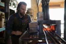 Blacksmith Heating Iron In Bla...