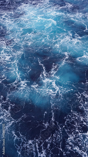 Dark water of the pacific ocean. Natural blue background. foam composition in the ocean. white sea foam, waves, storm. vertical photo