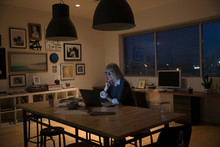 Dedicated Senior Businesswoman Working Late At Laptop In Studio Office